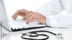 Image: A physician's hands on a laptop with a stethoscope next to it; Copyright: panthermedia.net/Rangizzz