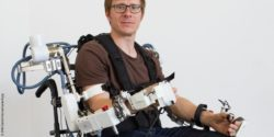 Image: Man in a wheelchair with robotic-supported system on the upper body; Copyright: DFKI GmbH/Annemarie Popp