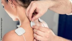 Image: Physician attaches electrodes to the upper back of a young woman; Copyright: panthermedia.net/microgen