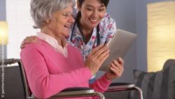 Image: elderly woman in a wheelchair showing a nurse something on a tablet; Copyright: panthermedia.net/mark@rocketclips.com