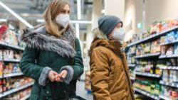 Image: A woman and a boy in a shop wearing facemasks; Copyright: PantherMedia/Arne Trautmann