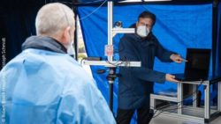 Image: man with a laptop and facemask explains something to another man in a tent; Copyright: Robert Bosch Hospital/Christoph Schmidt