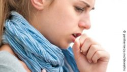 Image: young woman wearing a scarf and coughing; Copyright: panthermedia.net/alexraths