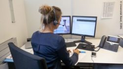 Image: View over the shoulder of a woman with a headset at her desk with two monitors and telephone; Copyright: Universität Basel, DSBG