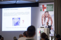 Image: Speaker on stage at MEDICA MEDICINE + SPORTS CONFERENCE
