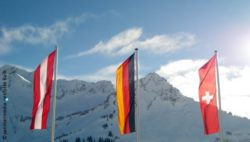 Photo: Flags of Germany, Austria and Switzerland in front of the Alps; Copyright: panthermedia.net/Silke Balk