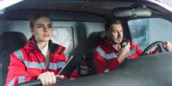 Image: Two paramedics in the driver's cab of an ambulance, one is using the radio; Copyright: panthermedia.net/Artur Verkhovetskiy