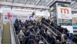 Image: Entrance area of MEDICA with escalator and many visitors; Copyright: Messe Düsseldorf