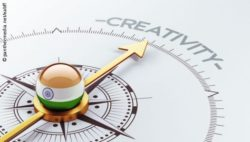"Image: Compass whose needle points to the word ""creativity"". In the hub of the compass is a ball which shows the Indian flag; Copyright: panthermedia.net/eabff"