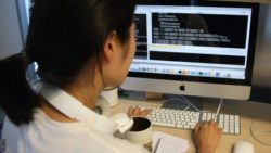 Image: look over the shoulder of a female researcher at a computer; Copyright: CRG