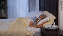 Image: Woman sleeping sideways in bed with a breathing mask; Copyright: Philips GmbH