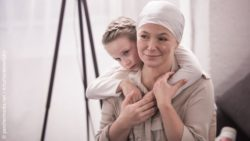 Image: woman with breast cancer and child in her arms; Copyright: panthermedia.net / ArturVerkhovetskiy