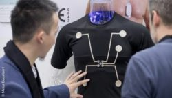 Image: Trade fair visitors look at a shirt with integrated sensors; Copyright: Messe Düsseldorf