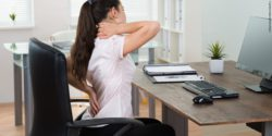 Image: Woman at her desk holding her back; Copyright: panthermedia.net/Andrey Popov