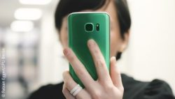 Image: A woman holding a smartphone in front of her head; Copyright: Fabian Eggert/IPU Berlin