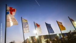 Image: Flags are blowing in the wind to the backdrop of a dark evening sky; Copyright: Messe Düsseldorf/ctillmann