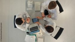 Image: three men at a table with laptop and tablet from above; Copyright: PantherMedia/FancyStudio