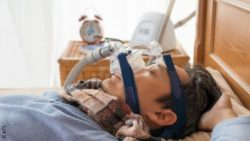 Image: Man is lying in bed asleep with CPAP; Copyright: ATS