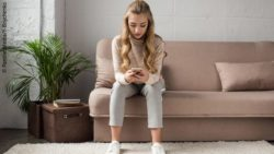 Image: young woman sitting on the couch with a smartphone; Copyright: PantherMedia/Y-Boychenko