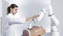 Image: Robot arm from KUKA, next to it a woman in a doctor's coat; Copyright: KUKA Deutschland GmbH