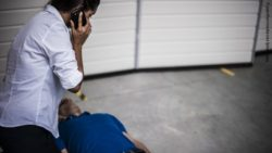 Image: young woman kneels next to unconscious man and makes call with smartphone; Copyright: panthermedia.net/pixelaway