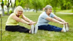 Image: Two women, one in older and one in middle years, are exercising at a meadow; Copyright: panthermedia.net/pressmaster