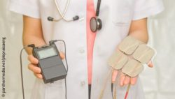 Image: Female physician holding a TENS device in one hand, electrodes in the other; Copyright: panthermedia.net/plepraisaeng