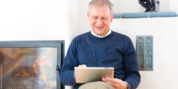 Photo: Older man sits in his living room, using a tablet; Copyright: panthermedia.net/Arne Trautmann