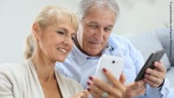 Image: Older couple is sitting next to each other, using their smartphones; Copyright: panthermedia.net/Fabrice Michaudeau