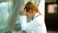 Image: Female doctor is leaning against a window with closed eyes, her hands holding her head ; Copyright: panthermedia.net/Slphotography