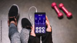 Image: Smartphone with a health app in the hands of a young woman in the gym; Copyright: PantherMedia/KostyaKlimenko