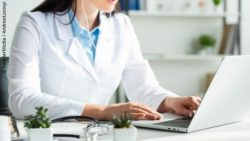 Image: a female doctor is sitting in front of a white laptop; Copyright: PantherMedia  / Andrew Lozovyi