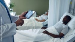 Image: A physician with a tablet computer in one hand is standing next to a patient's bed; Copyright: PantherMedia/Wavebreakmedia LtD