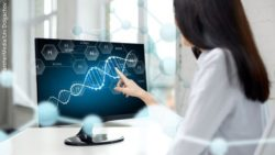 Image: A female researcher is sitting in front of a screen showing a DNA helix; Copyright: PantherMedia/Lev Dolgachov