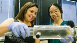 Image: Two female researchers are holding a transparent tube towards the camera; Copyright: University of Houston