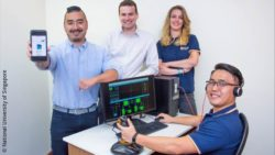 Image: team photo in which one man is holding a smartphone into the camera and one man sits in front of a computer; Copyright: National University of Singapore