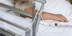 Image: Hand of a person in the hospital bed, next to the call button; Copyright: panthermedia.net/bignai