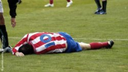 Photo: Football player motionless on the ground at the playing field; Copyright: panthermedia.net/pacoayala