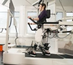 Image: Boy uses robotics on treadmill, next to it is a therapist; Copyright: Hocoma