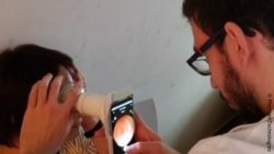 Image: physician examinates a patient with the portable device by holding the device and a smartphone in front of the patient's eye; Copyright: Phelcom Technologies