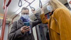 Image: A man and a woman with face masks standing next to each other in the subway, the man is using a smartphone; Copyright: PantherMedia/Arne Trautmann