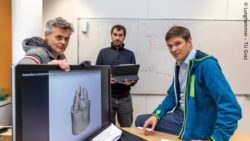 Image: three men sitting and standing behind a screen showing a computer model of the heart; Copyright: Lunghammer – TU Graz