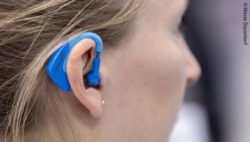 Image: Woman with a blue plug in her ear; Copyright: Messe Düsseldorf