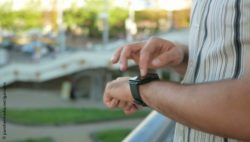 Image: A man is standing outdoors while typing on his smart watch; Copyright: panthermedia.net/guniamc