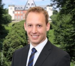 Image: Man with short blond hair, dark suit and tie in front of a castle - Dr. René Reiners; Copyright: Fraunhofer FIT