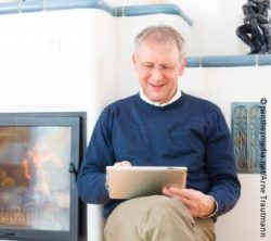 Photo: Man sitting in front of fireplace and reads with Tablet; Copyright: panthermedia.net/Arne Trautmann