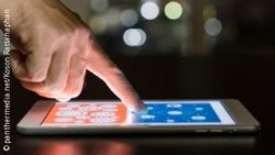 Image: A hand tips on a lying tablet; Copyright: panthermedia.net / Koson Rattanaphan