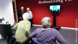 Image: Two elderly are sitting beside each other, looking on a screen, where a bingo game can be seen. One woman is standing up; Copyright: SilverFit, Robert ten Berge