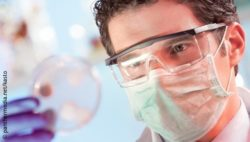 Image: Man with mouthguard and laboratory glasses holding Petri dish up; Copyright: panthermedia.net/kasto