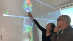Image: woman shows a man colorful radiation images projected on the wall; Copyright: UTSW